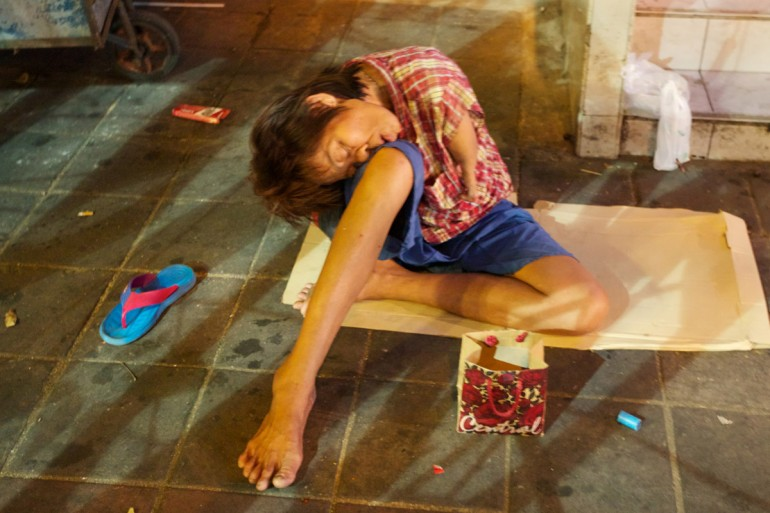 A one-armed beggar sits slumped on the street by his begging box.