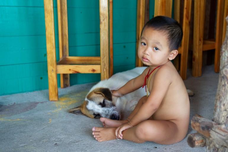 Little thai boy sitting petting an old dog on a concrete bar floor.