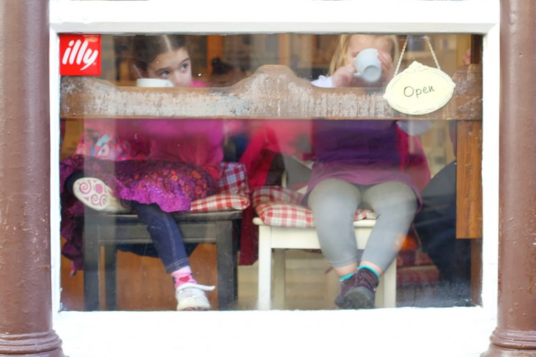 Two girls drinking from cups in a cafe window.