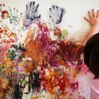 A little girl with smattered painted hand-prints along a wall.