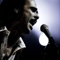 Nick Cave of Grinderman singing in spotlights