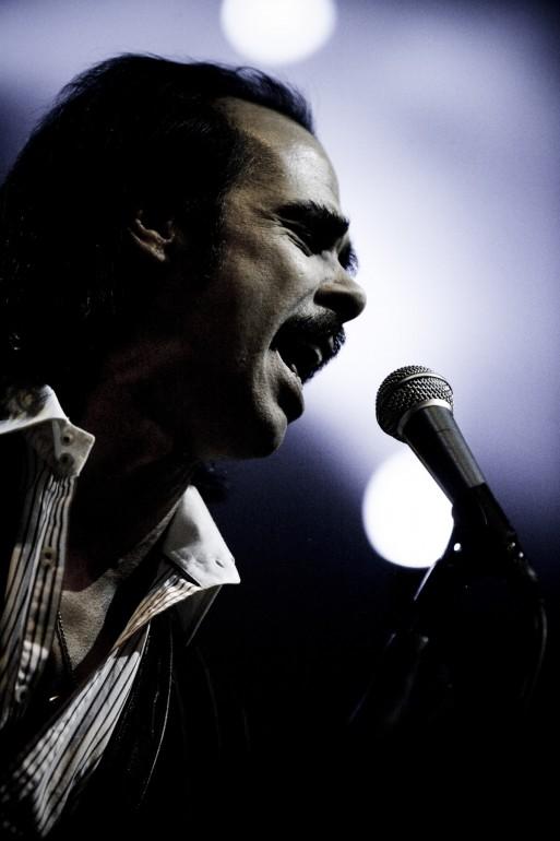 Nick Cave of Grinderman singing in spotlights