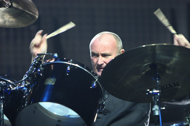 Phill Collins playing drums with intensity